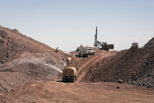 A truck sprays water near a drilling operation at the I-11 Boulder City Bypass construction project on Monday, July 18, 2016. The 12.5 miles of of highway is scheduled to open in late 2018. Jeff S ...
