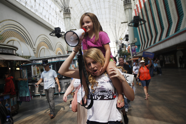 Maggie Bohl sits on her sister Melissa Score's shoulders at the March For Bernie USA demonstration at the Fremont Street Experience in downtown Las Vegas on Sunday, July 24, 2016. (Rachel Aston/La ...