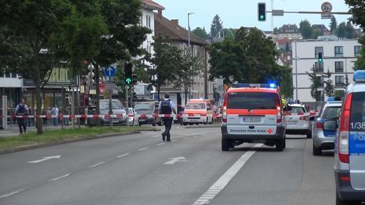 In this grab taken from video, police officers secure the area after a machete attack in Reutilingen, Germany, Sunday, July 24, 2016. A Syrian man killed a woman with a machete and wounded two oth ...