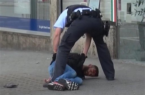 In this grab taken from video, police arrest a man in Reutilingen, Germany, Sunday, July 24, 2016. A Syrian man killed a woman with a machete and wounded two others Sunday outside a bus station in ...