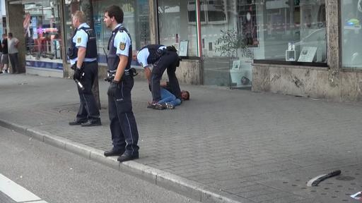 In this grab taken from video, police officers arrest a man close to a machete, front right, after an attack in Reutilingen, Germany, Sunday, July 24, 2016. A Syrian man killed a woman with a mach ...
