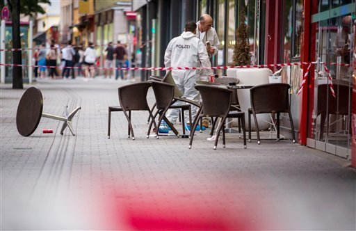 Police investigate the scene where a man killed a woman with a machete in Reutlingen near Stuttgart, southern Germany, Sunday, July 24, 2016. (Christoph Schmidt/dpa via AP)