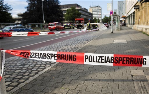 Police have cordoned off an area in inner city Reutlingen, Germany, Sunday, July 24, 2016. A man killed a woman with a machete and injured two other people in the area. The man has been arrested.  ...