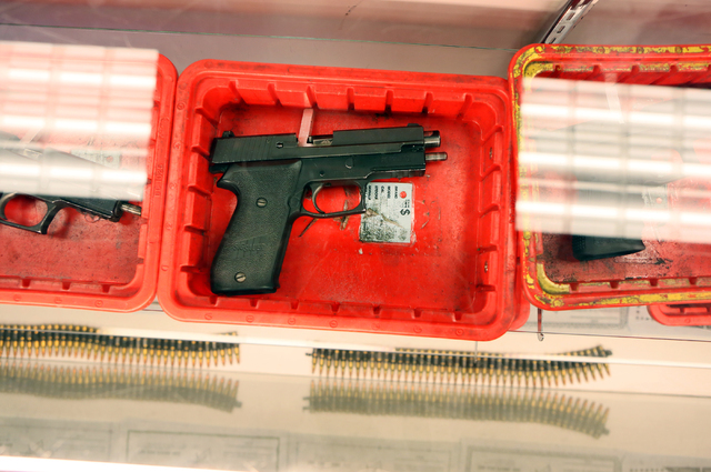 A handgun is shown under glass among assorted 40 and 45 caliber handguns at the indoor range check-in counter Monday, March 21, 2016, in Las Vegas. Ronda Churchill/Las Vegas Review-Journal