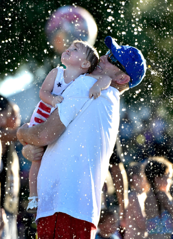 A father and daughter stand up amidst a shower of water during the Fourth of July celebration at Mission Hills Park Monday, July 4, 2016, in Henderson. David Becker/Las Vegas Review-Journal Follow ...