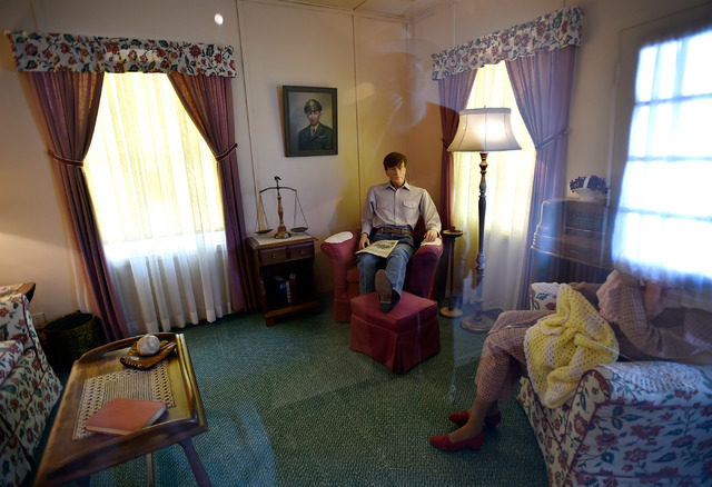 Clark County museums administrator Mark Hall-Patton is reflected in a glass partition protecting mannequins inside one of the rooms at the 1941 Henderson Townsite home at the Clark County Museum T ...