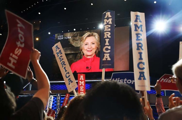 Attendees at the Democratic National Convention listen to a video message from Hillary Clinton at the Wells Fargo Center on Tuesday, July 26, 2016, in Philadelphia. (Benjamin Hager/Las Vegas Revie ...
