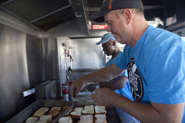 Founder of Goodness Gracious Ministries Brian Bland, a Henderson resident, left and Kevin Harris make grilled cheese sandwiches for the homeless July 19 in Las Vegas. Loren Townsley/View