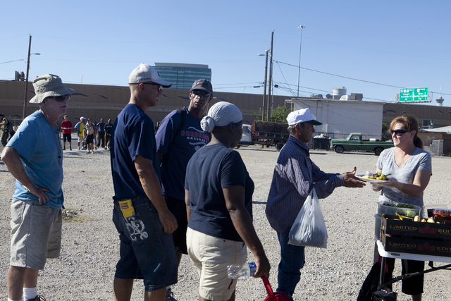 Lori Beasley, right, gives food to the homeless on the corner of G Street and McWilliams Avenue in Las Vegas July 19. Loren Townsley/View