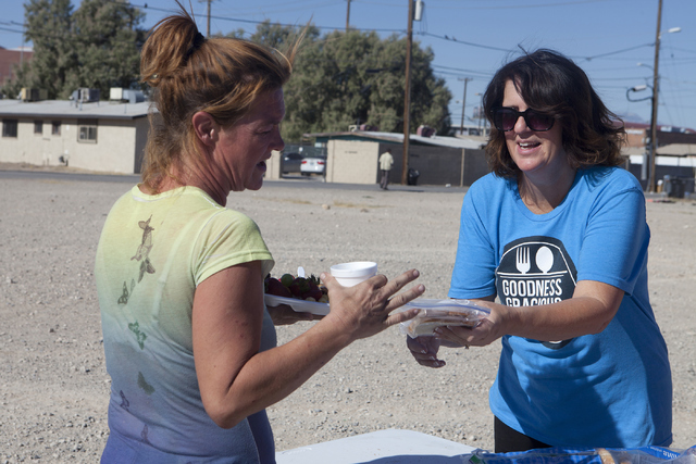 Goodness Gracious Ministries co-founder and Henderson resident Jenny Bland, right, offers peanut butter and jelly to a homeless woman on the corner of G Street and McWilliams Avenue in Las Vegas J ...