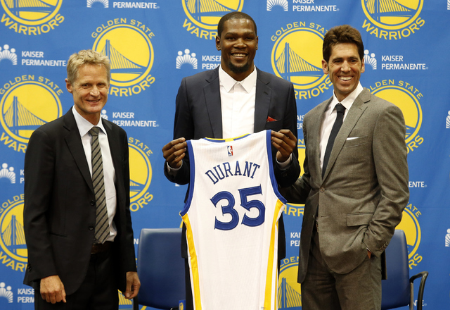 Golden State Warriors' newest player Kevin Durant, center, joins head coach Steve Kerr, left and general manager Bob Myers during a news conference at the NBA basketball team's practice facility,  ...