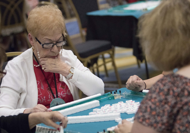 Sheila Horowitz, left, of Jacksonville, Fla. glances at her mahjong tiles while competing during the Mah Jongg World Championship at the Westgate Las Vegas hotel-casino in Las Vegas on Saturday, J ...