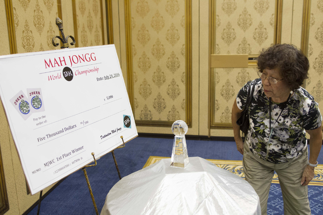 Mei Koehnen of Bradenton, Fla. looks at the $5000 prize and trophy for the winner of the Mah Jongg World Championship at the Westgate Las Vegas hotel-casino in Las Vegas on Saturday, July 23, 2016 ...