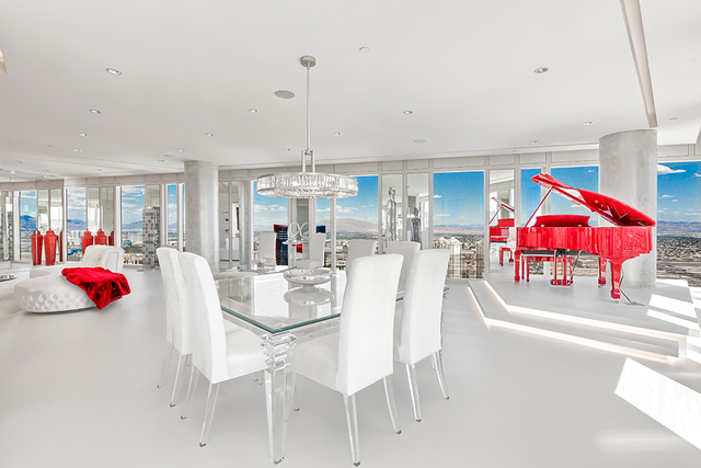 Courtesy of Luxury Estates International Large white Neolith tiles, white walls, white chairs situated around a glass-top table, and glass chandeliers created a blank canvas with floor-to-ceiling  ...