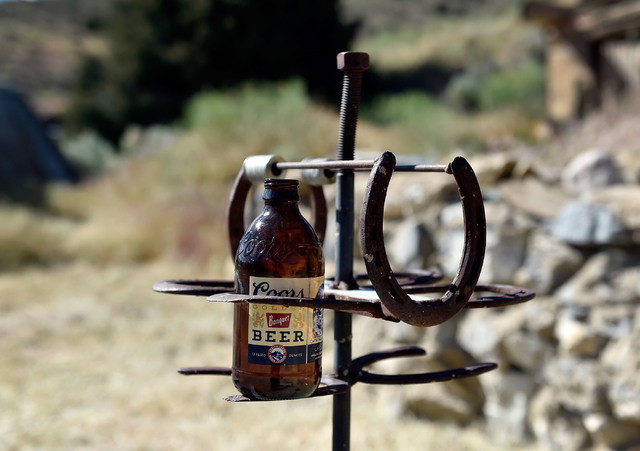 An empty bottle of beer is seen at the horseshoe pits behind the Manhattan Bar Thursday, June 9, 2016, in Manhattan, Nev. The old-time bar has served its customers for decades in the high desert m ...