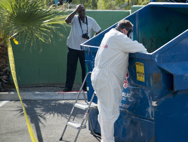 A man in a hazmat suit reaches into a dumpster as police and the Southern Nevada Health District investigate medical waste that was found inside at Hampton Court Apartments near Swenson Avenue and ...