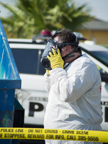 A man in a hazmat suit puts on his protective mask as police and the Southern Nevada Health District investigate medical waste that was found inside a dumpster at Hampton Court Apartments near Swe ...