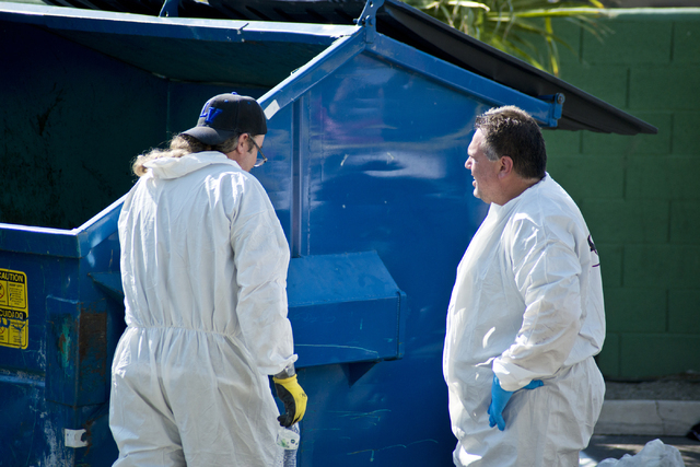 Two men in a hazmat suits take a break as police and the Southern Nevada Health District investigate medical waste that was found inside a dumpster at Hampton Court Apartments near Swenson Avenue  ...