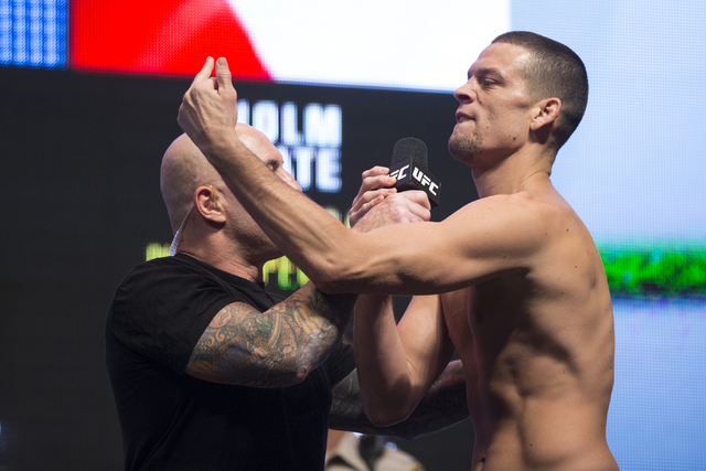 UFC fighter Nate Diaz gestures at his opponent Conor McGregor during their weigh-in event for UFC 196 at the MGM Grand Garden Arena on Friday, March 4, 2016, in Las Vegas. Diaz and McGregor will f ...
