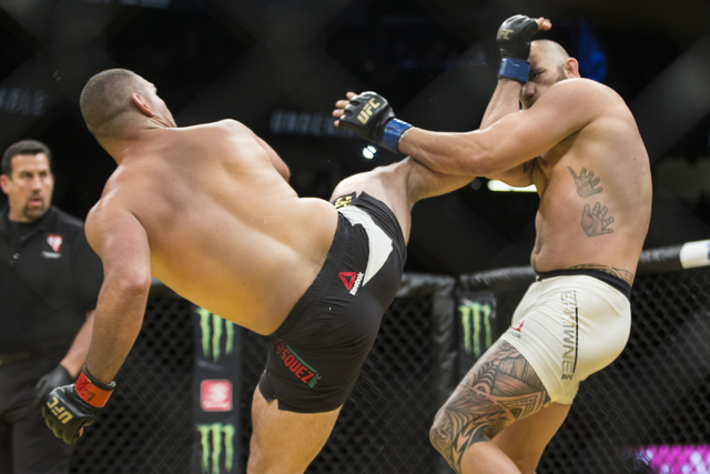 Cain Velasquez, left, connects a right kick against Travis Browne in the heavyweight bout during UFC 200 at T-Mobile Arena on Saturday, July 9, 2016, in Las Vegas. Velasquez won by technical knock ...