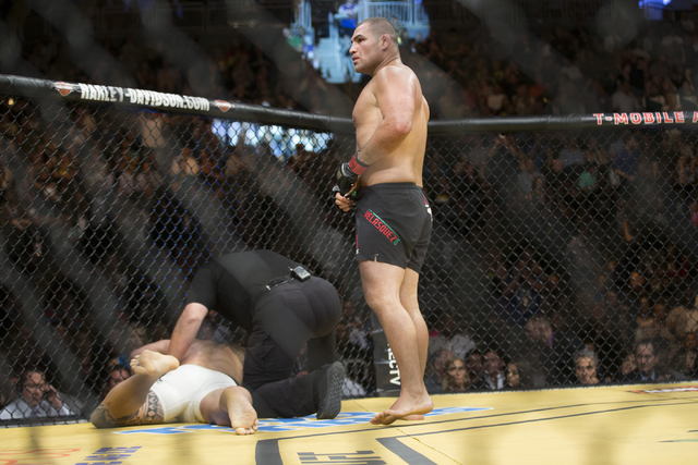 Cain Velasquez, right, stand over Travis Browne after a technical knockout win in the heavyweight bout during UFC 200 at T-Mobile Arena on Saturday, July 9, 2016, in Las Vegas. (Erik Verduzco/Las  ...