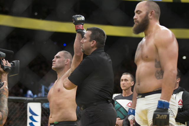 Cain Velasquez, left, raises his arm in victory against Travis Browne in the heavyweight bout during UFC 200 at T-Mobile Arena on Saturday, July 9, 2016, in Las Vegas. Velasquez won by technical k ...