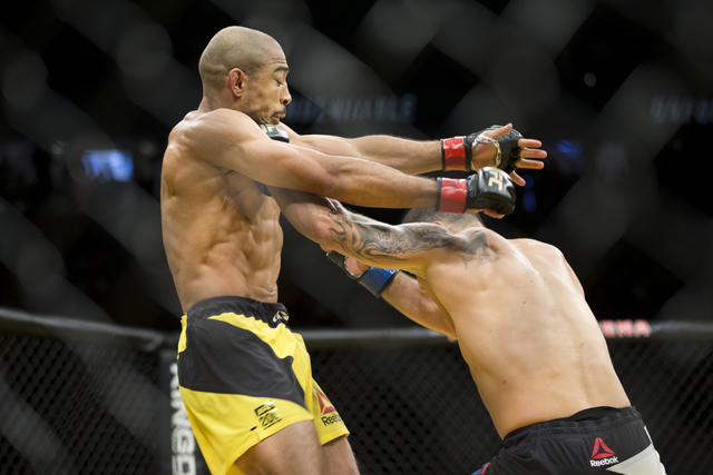 Jose Aldo, left, takes a punch against Frankie Edgar in the interim featherweight title bout during UFC 200 at T-Mobile Arena on Saturday, July 9, 2016, in Las Vegas. Aldo won by unanimous decisio ...