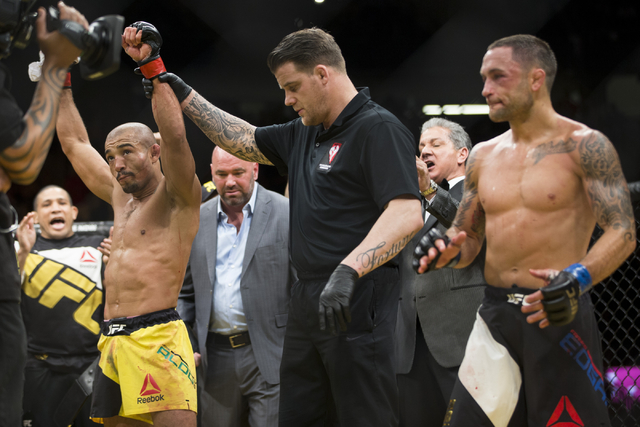 Jose Aldo, left, raises his arm in victory against Frankie Edgar in the interim featherweight title bout during UFC 200 at T-Mobile Arena on Saturday, July 9, 2016, in Las Vegas. Aldo won by unani ...