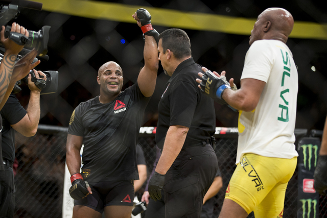 Daniel Cormier, left, raises his arm in victory against Anderson Silva in the light heavyweight bout during UFC 200 at T-Mobile Arena on Saturday, July 9, 2016, in Las Vegas. Cormier won my unanim ...