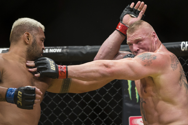 Mark Hunt, left, connects a left punch against Brock Lesnar in the heavyweight bout during UFC 200 at T-Mobile Arena on Saturday, July 9, 2016, in Las Vegas. Lesnar won by unanimous decision. (Eri ...