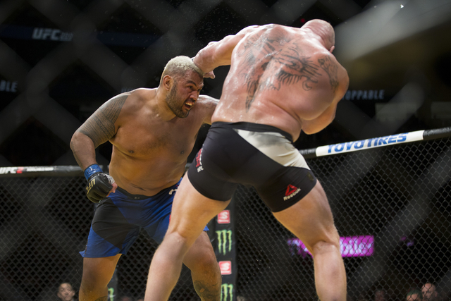 Mark Hunt, left, battles Brock Lesnar in the heavyweight bout during UFC 200 at T-Mobile Arena on Saturday, July 9, 2016, in Las Vegas. Lesnar won by unanimous decision. (Erik Verduzco/Las Vegas R ...