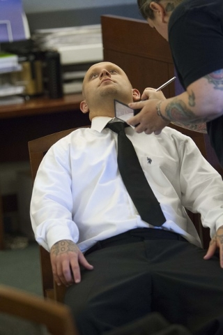 A makeup artist applies a touch up coat of makeup that conceal the tattoos on the face and neck of Bayzle Morgan while on a break during jury selection in his trial at the Regional Justice Center  ...