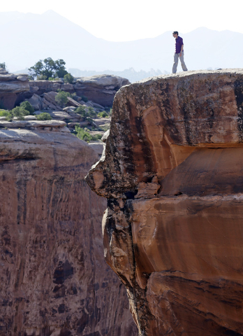 U.S. Interior Secretary Sally Jewell looks into a canyon at Gemini Bridges during a tour Thursday, July 14, 2016, near Moab, Utah. (Rick Bowmer/The Associated Press)
