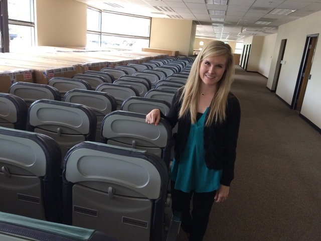 Kellie Wyatt, marketing special for Make-A-Wish, takes a seat May 17 in one of the airline seats currently in storage at the space Make-a-Wish will occupy as its new headquarters. The interior wil ...