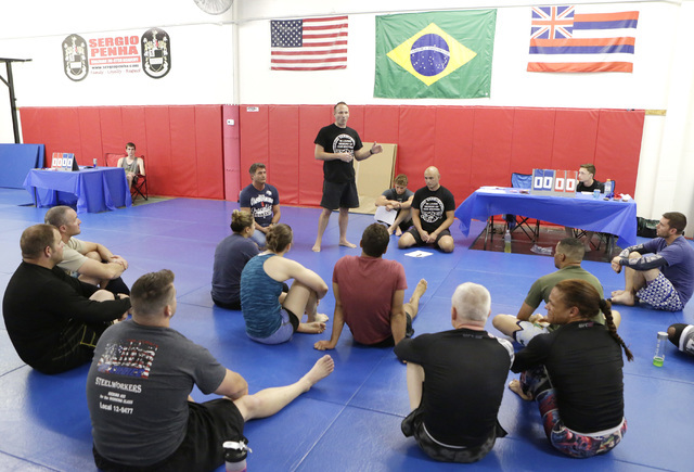Sgt. Dave Callen, of Las Vegas Metro police speaks to participants prior to the start of the 2016th officer David VanBuskirk-Memorial Grappling Event at Sergio Penha's Brazilian Jiu-Jitsu Academy  ...