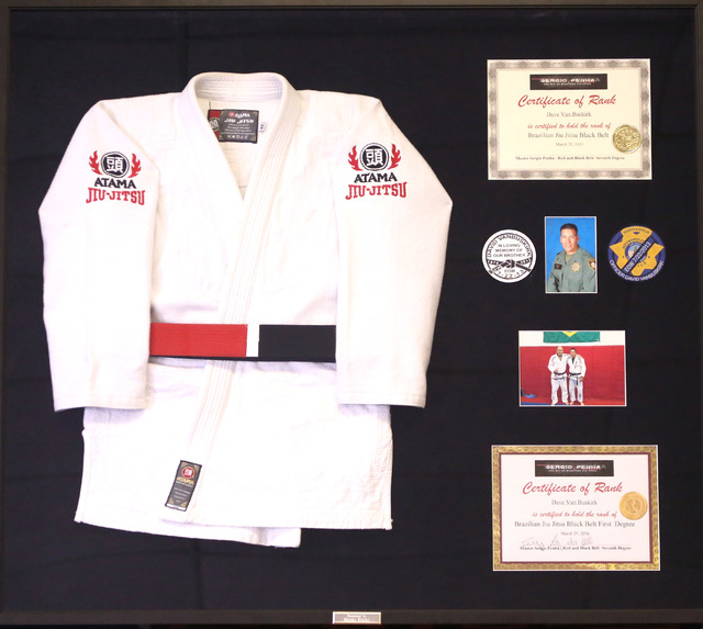 Metro Officer David Vanbuskirk's framed Grappling gi and his certificates of rank is displayed at Sergio Penha's Brazilian Jiu-Jitsu Academy on Saturday, July 30, 2016, where police officers and f ...