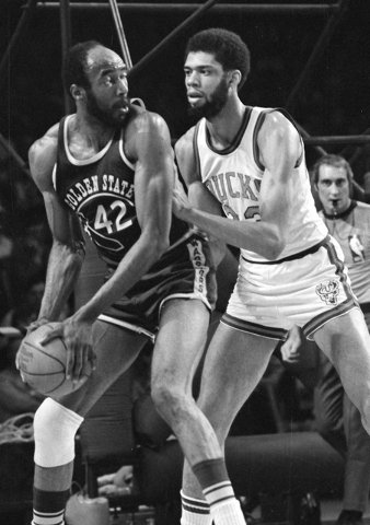In this March 30, 1973, file photo, Nate Thurmond of the Golden State Warriors (42) looks back at Kareem Abdul-Jabbar of the Milwaukee Bucks before making his move toward the basket during NBA pla ...