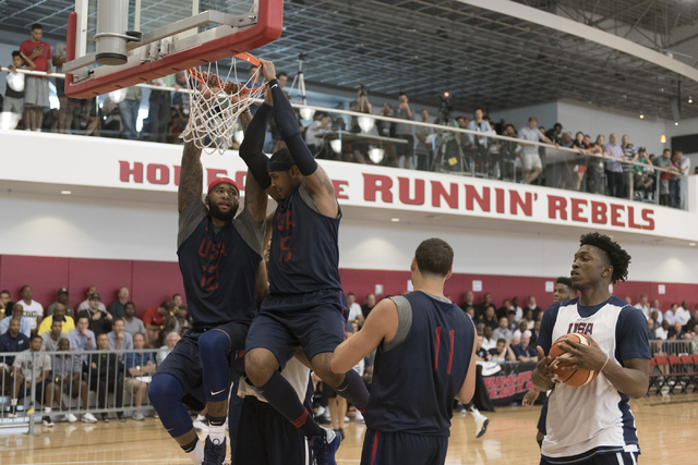 Center DeMarcus Cousins (12), left, and forward Carmelo Anthony (15) simultaneously hang off the rim following a layup attempt during a USA men's basketball Olympic team practice at UNLV's Mendenh ...