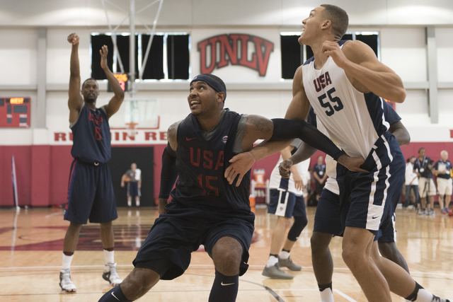 Forward Carmelo Anthony (15), center, positions himself for a rebound as forward Harrison Barnes (8), left, shoots a free throw during a USA men's basketball Olympic team practice at UNLV's Menden ...
