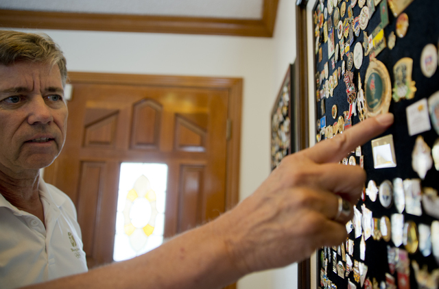 Larry Brickner looks at his collection of olympic pins inside his Las Vegas home on Sunday, July 24, 2016. Brickner will be attending his eleventh Olympic Games when he travels to Rio de Janeiro,  ...