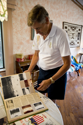 Larry Brickner looks at some of his Olympic Games memorabilia in his Las Vegas home on Sunday, July 24, 2016. Brickner will be attending his eleventh Olympic Games when he travels to Rio de Janeir ...