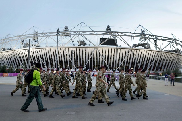 Members of the British military march by Olympic Stadium before the closing ceremony of the 2012 Summer Olympics in London, Aug. 12, 2012. The players' association says Major League Baseball has g ...