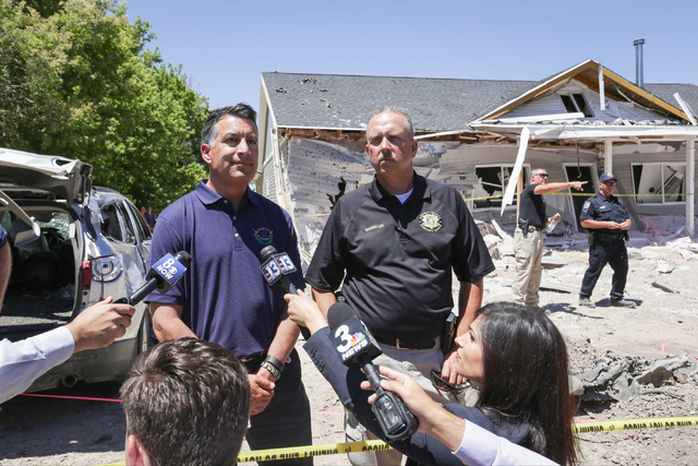 Nevada Governor Brian Sandoval, left, speaks to the media and community members with Lincoln County Sheriff Kerry Lee on Friday, July 15, 2016, at the attacked house in Panaca, Nev. (Brett Le Blan ...