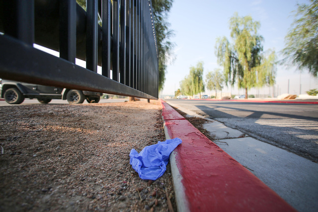 A medical glove lies discarded on a curb at Big League Dreams park near where Las Vegas police say a shooting erupted when a man in a vehicle attempted to rob Pokemon Go players early Monday morni ...