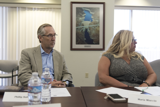Phillip Holt, managing director with the National Installment Lenders Association, left, and Maria Miuccio, owner of Cash Kingdom, listen during a summit to discuss payday loans and their dangers  ...