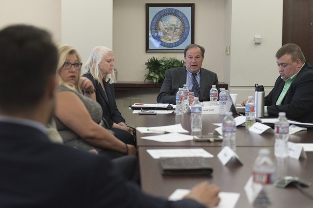 Nevada Treasurer Dan Schwartz, second from right, speaks with business owners and lobbyists during a summit to discuss payday loans and their dangers at the Sawyer Building in Las Vegas Friday, Ju ...