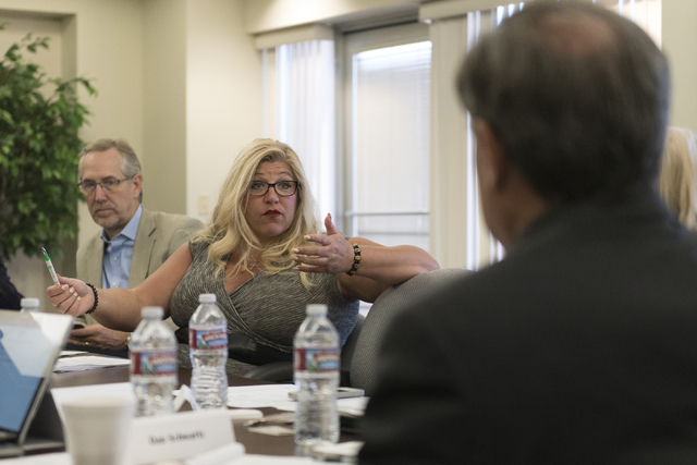 Maria Miuccio, owner of Cash Kingdom, center, speaks to Nevada Treasurer Dan Schwartz, right, during a summit to discuss payday loans and their dangers at the Sawyer Building in Las Vegas Friday,  ...