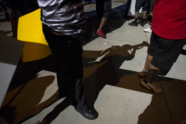 A helicopter casts a shadow down onto a protester speaking on a microphone on the evening of Saturday, July 9, 2016 at Martin Luther King Boulevard and Carey Avenue in Las Vegas. (Bridget Bennett/ ...