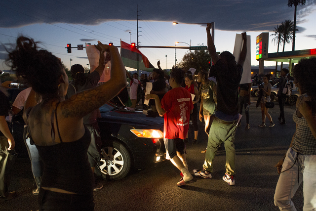 A car drives through the crowd as demonstrators occupy the intersection of Martin Luther King Boulevard and Carey Avenue on Saturday, July 9, 2016, in Las Vegas. (Bridget Bennett/Las Vegas Review- ...