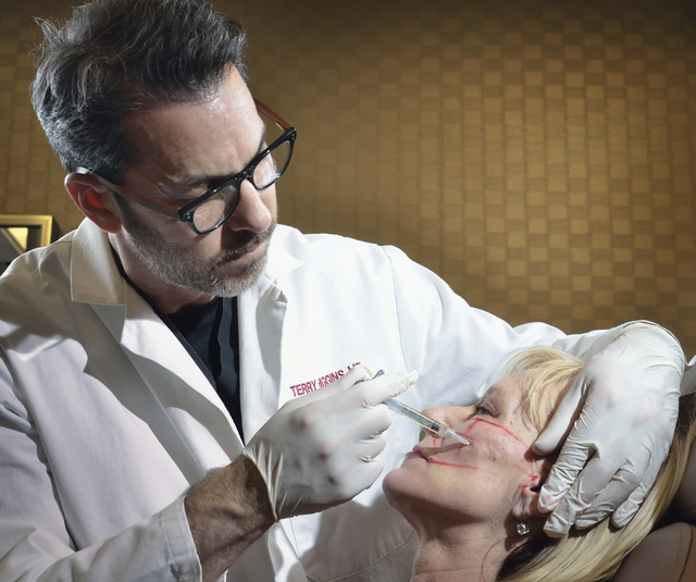 Dr. Terry Higgins injects a patient with a compound used to fill hollows in the face and make cheekbones look fuller at Anson and Higgins Plastic Surgery Associates in this file photo. (Bill Hughe ...